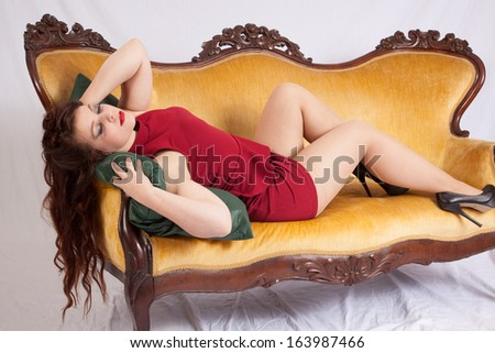 Pretty Caucasian woman in a short red dress, sitting on an old couch and looking with a relaxed flirting expression