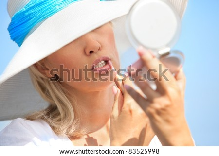Pretty caucasian woman putting lipstick on - stock photo
