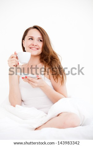 Pretty Caucasian woman sitting on a bed with a cup on a light background - stock photo