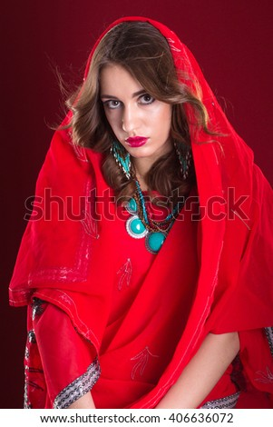 Pretty caucasian woman wearing in red indian sari and scarf on her head, close up portrait