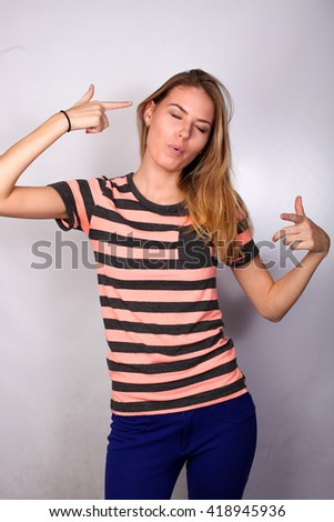 Pretty caucasian young blonde woman student posing in the studio isolated on white background. She folded her hands in the form of a gun - stock photo