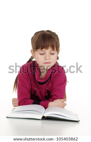 Pretty Caucasian young girl lying with a book on a white background