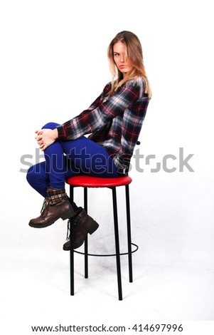 pretty charming girl Caucasian blonde in a plaid shirt and blue pants sitting on a bar stool , isolated on white - stock photo