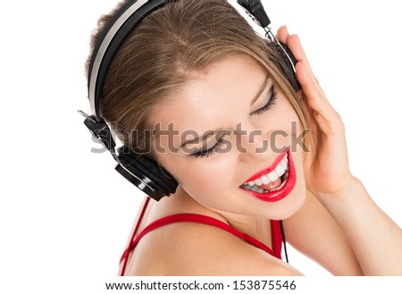 Pretty cheerful lady in red singing and listening song on headphones, isolated over white background. Young attractive happy showgirl posing in studio.  - stock photo