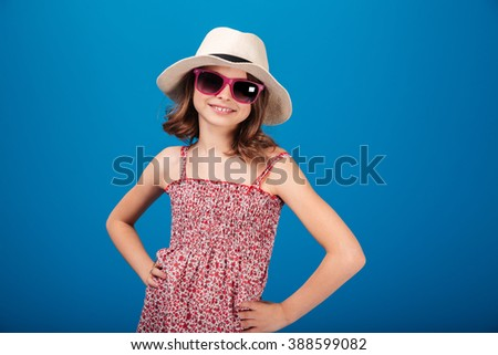 Pretty cheerful little girl in hat and glasses standing over blue background - stock photo