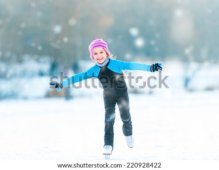 pretty  cheerful little girl in thermal suits skating  outdoors - stock photo