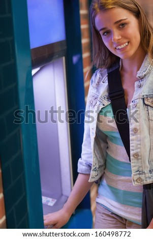 Pretty cheerful student withdrawing cash smiling at camera at an ATM - stock photo