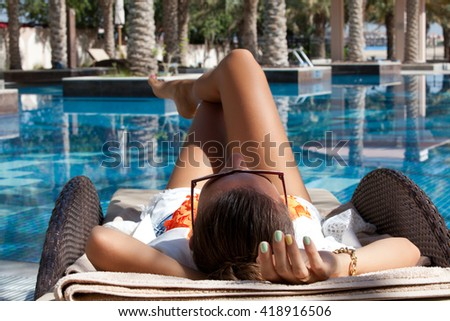 Pretty cheerful woman holding hand behind head, relaxing at the luxury poolside. Girl at travel spa resort pool. Summer luxury vacation.  - stock photo