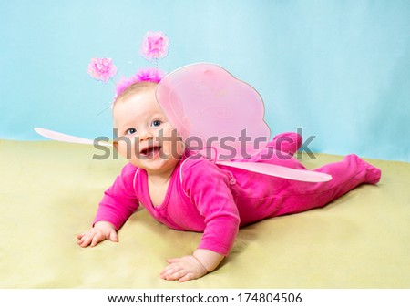 Pretty child girl, dressed in butterfly costume on  background The concept of childhood and holiday - stock photo