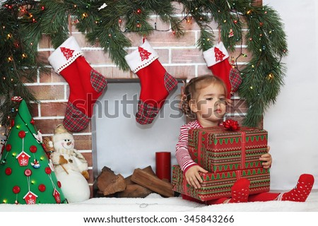 Pretty child girl holding some packed gifts near Christmas decorated fireplace, winter holiday family concept - stock photo