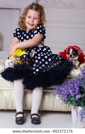 Pretty child girl is holding two small dogs - stock photo
