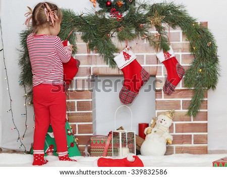 Pretty child girl looking for a gift in Santa sock near Christmas decorated fireplace, winter holiday family concept - stock photo