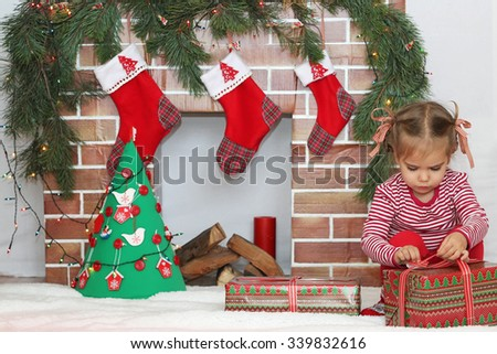 Pretty child girl opening a gift near Christmas decorated fireplace, winter holiday family concept - stock photo