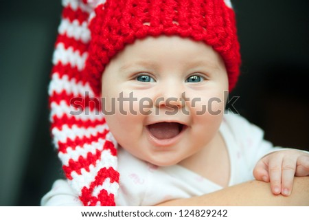 pretty child of tender years in red hat smiling - stock photo