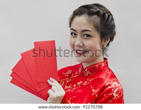 pretty chinese young woman holding red bags for happy chinese new year