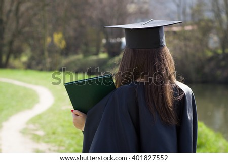 Pretty clever college / university student / girl after graduation day / completion ceremony wearing gown and mortarboard and enjoying completion during lovely sunny day - stock photo