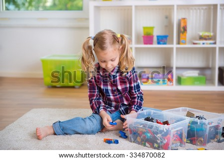 Pretty clever girl play with toy blocks at home - stock photo