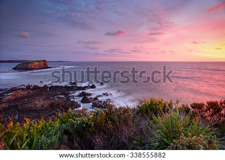 Pretty clouds light up at sunrise with views from the Minamurra headland overlooking the exposed volcanic rocks below and Stack Island.  Water and some foreground leaves in motion - stock photo