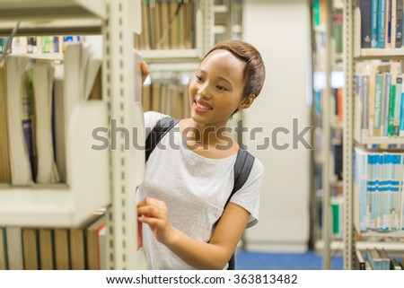 pretty college girl searching for book in library
