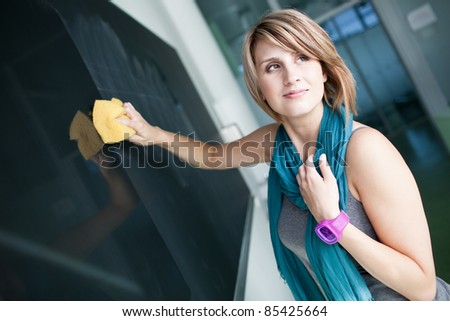 pretty college student erasing the chalkboard/blackboard during a math class (color toned image; shallow DOF) - stock photo