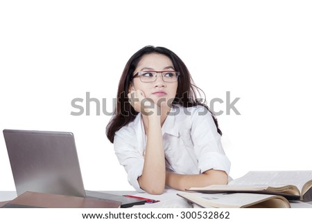 Pretty college student with long hair and wearing glasses, daydreaming about her dream with laptop and books on the table, isolated on white - stock photo