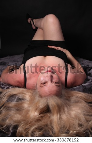 Pretty, confident, middle aged woman in her fifties laying on a dark background - stock photo