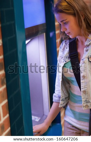 Pretty content student withdrawing cash at an ATM - stock photo
