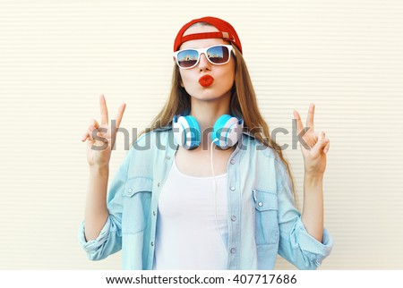 Pretty cool woman in sunglasses and red cap having fun over white background - stock photo