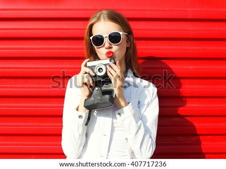 Pretty cool woman with retro camera over red background - stock photo