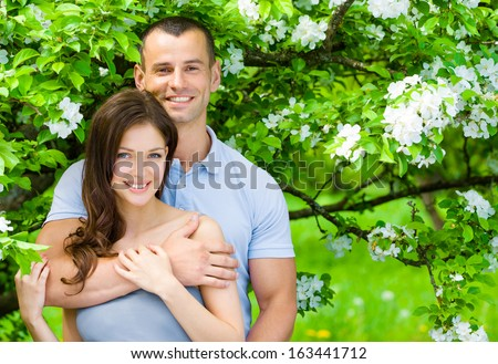 Pretty couple embracing near blossomed tree in the park. Concept of love and stable relations - stock photo