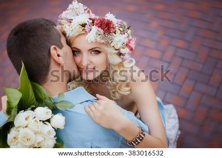 Pretty couple hugging and flirting in an urban park He kisses her, she smiles and looks into the camera a wreath on his head, holding flowers in their hands summer - stock photo