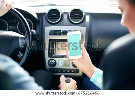 Pretty couple sitting in new automobile and holding mobile phone, copy space, green mock up.