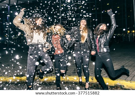 Pretty crazy girls dancing, throwing confetti and having fun - Young women partying outdoors before to go in a club - stock photo