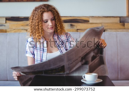 Pretty curly hair girl having cup of coffee and reading newspaper at the cafe - stock photo