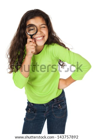 Pretty cute caucasian girl wearing a green long sleeve top and blue jeans. She is playing with a magnifying glass. - stock photo