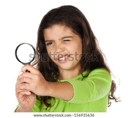 Pretty cute caucasian girl wearing a green long sleeve top. She is playing with a magnifying glass. - stock photo
