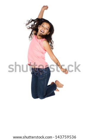 Pretty cute caucasian girl wearing a pink top and blue jeans. The girl is jumping and smiling. - stock photo