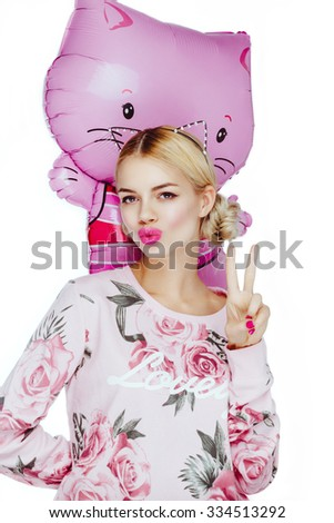Pretty cute young blond girl posing in studio, looking at camera taking in hands a balloon pink cat. - stock photo