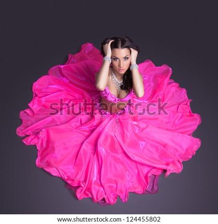 Pretty dancer in pink costume sitting on floor - stock photo