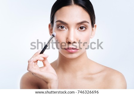 Pretty dark-haired woman holding makeup brush