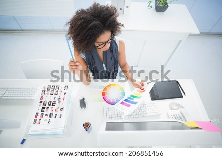Pretty designer working at her desk in her office - stock photo