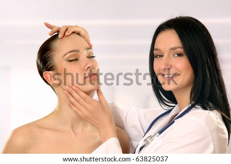 Pretty doctor examining beautiful young female's face