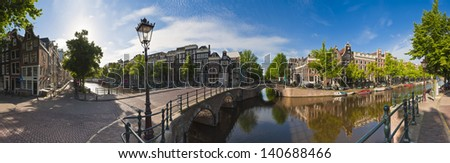 Pretty dutch doll houses reflected in the tranquil canals of Amsterdam. - stock photo