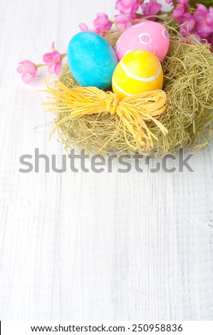 Pretty Easter Eggs in Nest with Pink Flowers in top of framework on Rustic Painted Wood boards with blank, empty room or space for copy, text, your words.  Vertical above view, closeup. - stock photo