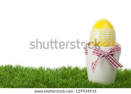 Pretty Easter gift with a decorative yellow Easter Egg inside a flower pot tied with a rustic red and white checked ribbon and bow standing on green grass against a white background with copyspace - stock photo