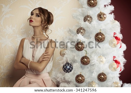 pretty elegant girl with hair-style and fashion dress sitting near christmas decorated tree in indoor shoot with serious expression  - stock photo