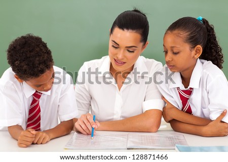 pretty elementary school teacher helping students in classroom - stock photo