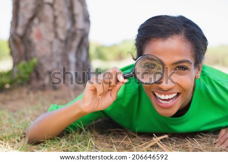 Pretty environmental activist looking at camera through magnifying glass on a sunny day in the countryside - stock photo