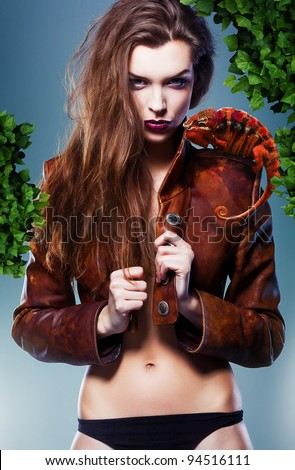 pretty erotic devil woman in leather jacket with chameleon under tree - stock photo