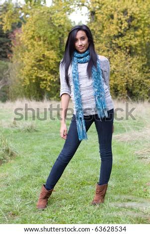 Pretty ethnic girl enjoying the fall season. - stock photo